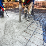 a photo showing concrete being poured onto a reinforcement mesh